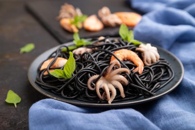 Pâtes à l'encre de seiche noire aux crevettes ou crevettes et petits poulpes sur fond de béton noir et textile bleu. vue de côté, gros plan,