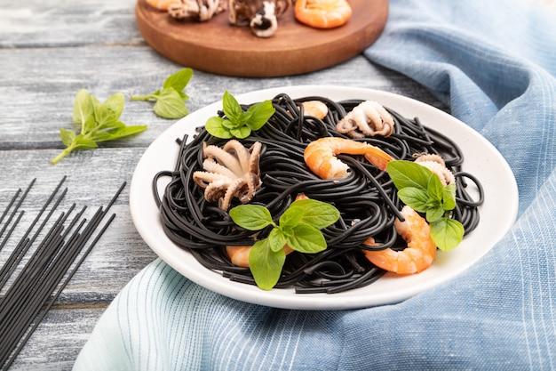 Pâtes à l'encre de seiche noire aux crevettes ou crevettes et petits poulpes sur fond de bois gris et textile bleu. vue de côté,
