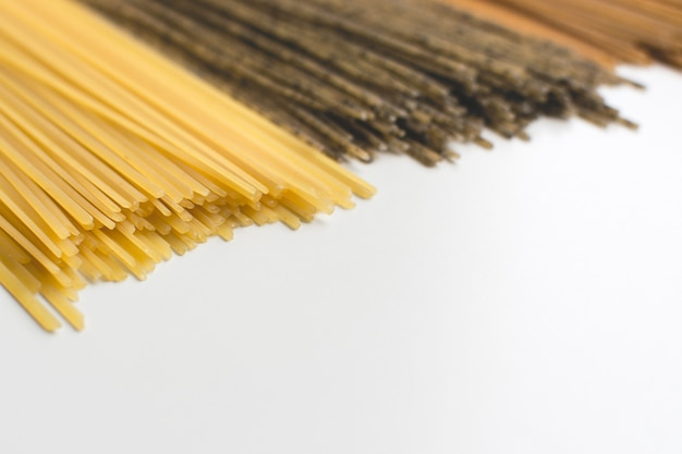 Pâtes entières spaghetti tricolora sur fond blanc