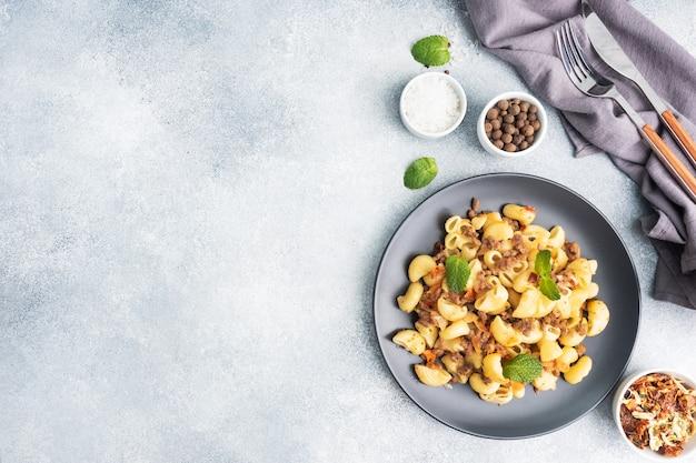 Pâtes à l'étouffée avec boeuf haché et légumes, macaronis à la marine sur une assiette. fond de béton gris. espace de copie.
