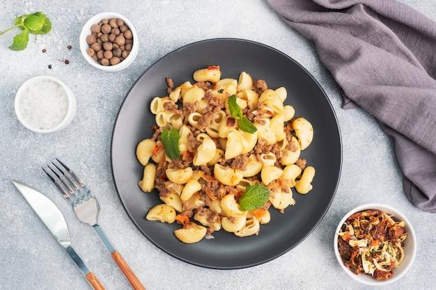 Pâtes à l'étouffée avec boeuf haché et légumes, macaronis à la marine sur une assiette. fond de béton gris.