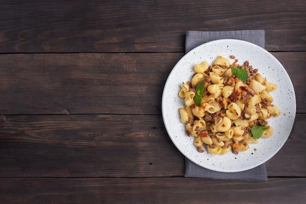 Pâtes à l'étouffée avec boeuf haché et légumes, macaronis à la marine sur une assiette. fond en bois sombre. espace de copie.