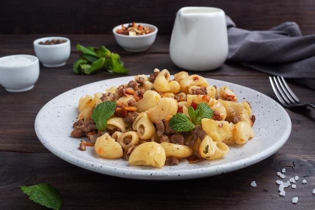 Pâtes à l'étouffée avec boeuf haché et légumes, macaronis à la marine sur une assiette. fond en bois sombre.