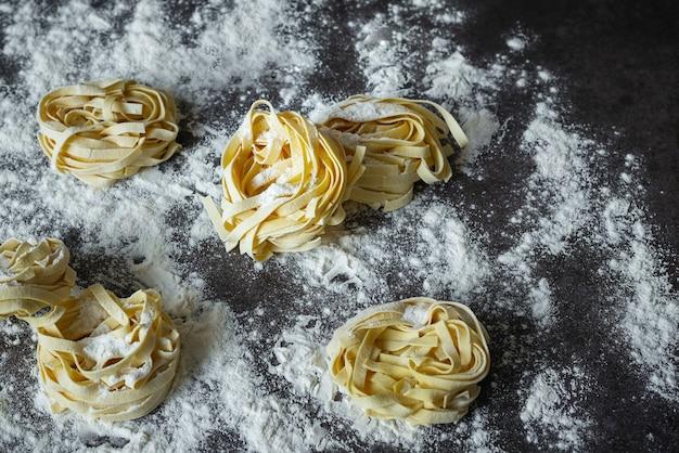 Les pâtes faites à la main des tagliatelles crues avec de la farine sur une table sombre