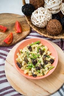 Pâtes faites maison aux champignons et légumes: haricots et pois dans une assiette.