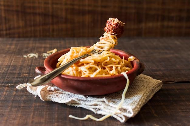 Pâtes faites maison avec boulette de viande dans la faïence sur la serviette sur la table en bois