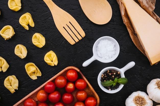 Pâtes farcies et ustensiles près des ingrédients de cuisine