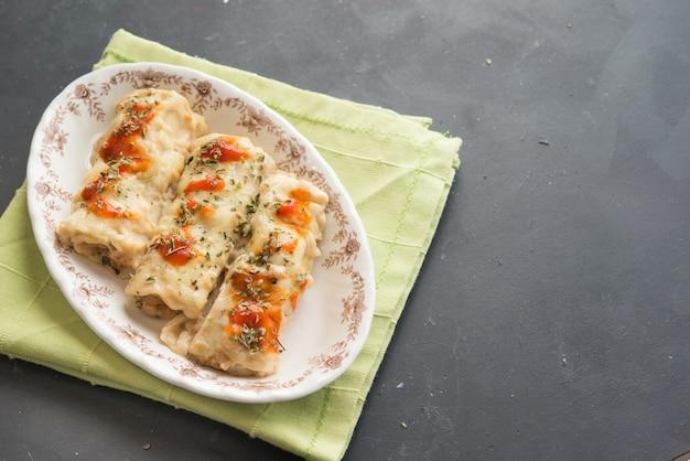 Pâtes farcies à la viande dans une assiette. cannellonis italiens, canelones espagnols avec serviette verte