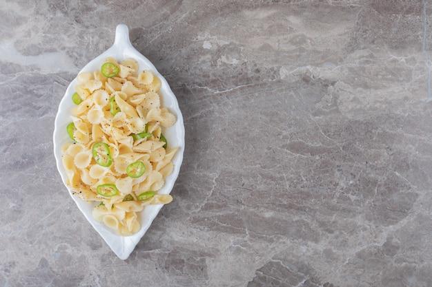 Pâtes farfalle au poivre sur une assiette fantaisie , sur la surface en marbre.