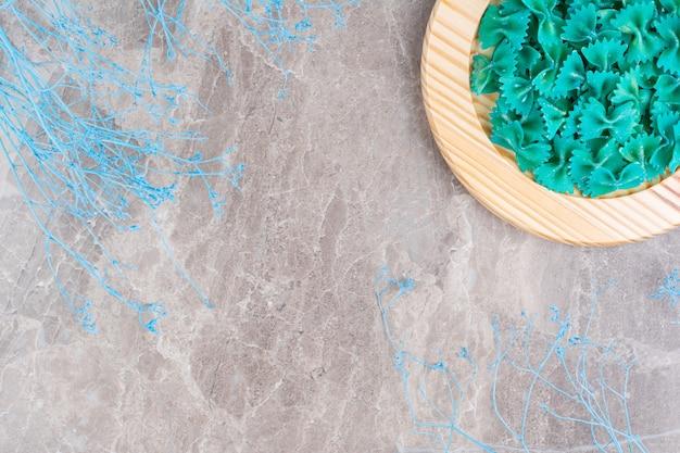Pâtes farfalle bleues sur une assiette en bois, sur le marbre.