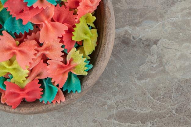 Pâtes farfalle colorées dans un bol en bois.