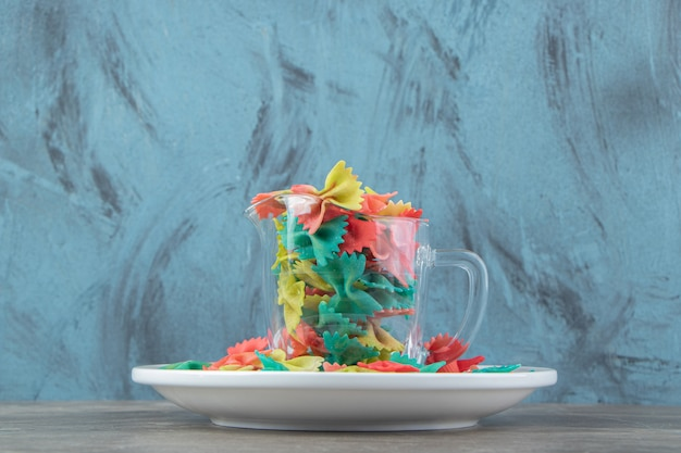 Pâtes farfalle colorées dans une tasse en verre