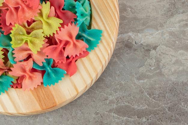 Pâtes farfalle colorées sur plaque de bois.