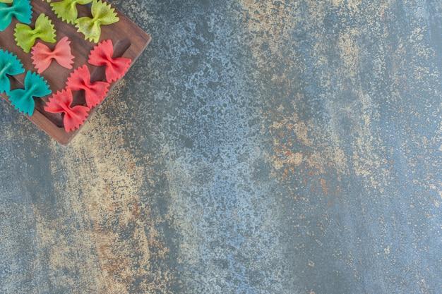 Pâtes farfalle colorées sur le plateau, sur le fond de marbre.
