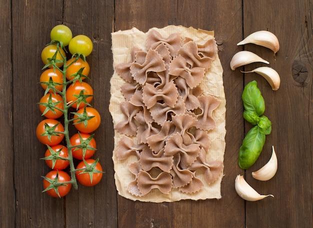 Pâtes farfalle crues, basilic et légumes sur fond de bois
