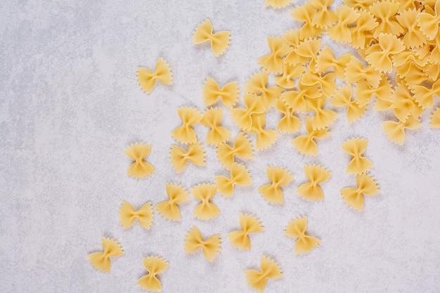 Pâtes farfalle crues sur surface blanche