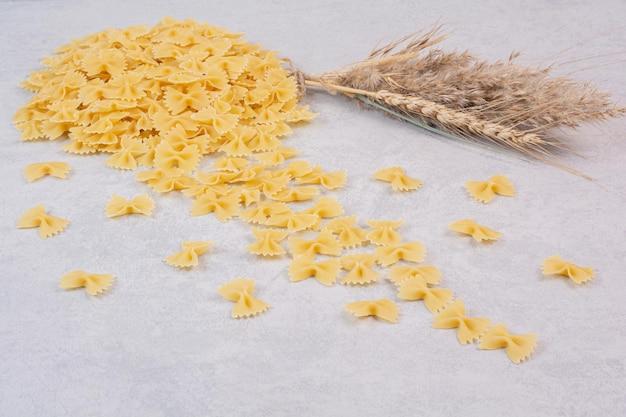Pâtes farfalle crues sur table blanche avec du blé.