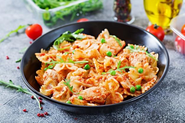 Pâtes farfalle avec filet de poulet, sauce tomate et petits pois. repas italien. le menu