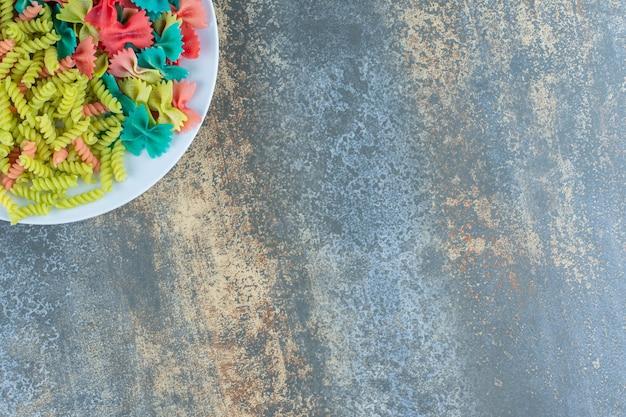 Pâtes farfalle et fusilli dans l'assiette, sur fond de marbre.