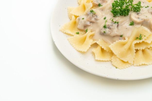 Pâtes farfalle avec sauce crème blanche aux champignons isolé sur fond blanc