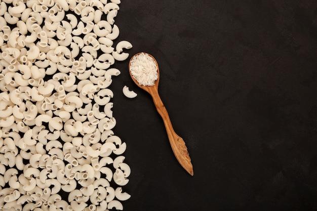 Pâtes à la farine de riz et riz blanc dans une cuillère en bois vue de dessus espace de copie de fond texturé foncé