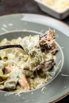 Pâtes fettuccine alfredo aux champignons et poulet frit dans une sauce crémeuse au fromage. pâtes tagliatelles. fond de recette de nourriture. fermer.