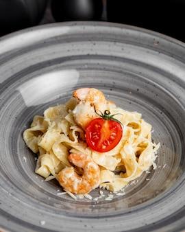 Pâtes fettuccine aux crevettes tomates et fromage râpé