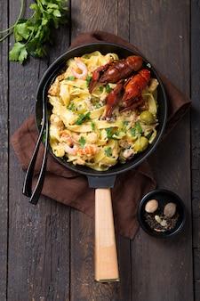 Pâtes fettuccine aux fruits de mer avec écrevisses, crevettes de poulpe, sur poêle en pierre. plat gourmand