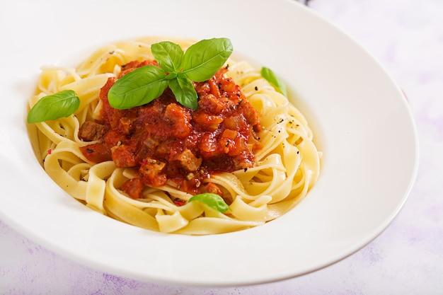 Pâtes fettuccine bolognaise à la sauce tomate dans un bol blanc.