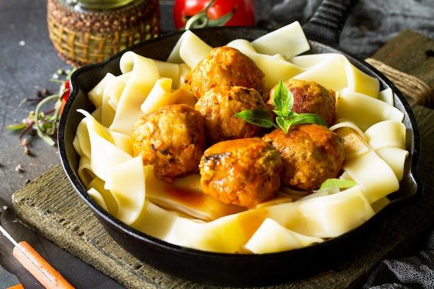 Pâtes fettuccine et boulettes de boeuf maison à la sauce tomate dans une poêle à frire sur une table en pierre sombre
