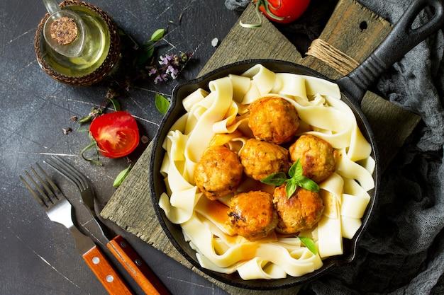 Pâtes fettuccine et boulettes de viande de boeuf maison à la sauce tomate dans une poêle à frire vue de dessus