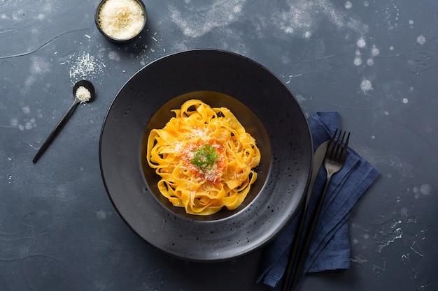 Pâtes fettuccine avec sauce passat italienne traditionnelle et fromage parmesan dans une assiette lumineuse sur fond de béton blanc ancien. vue de dessus.