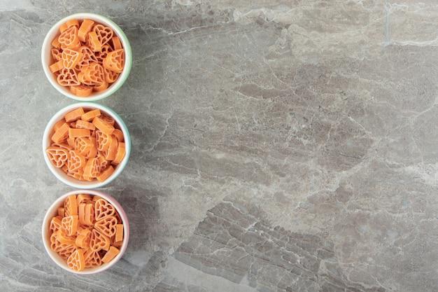 Pâtes en forme de coeur non cuites dans des bols colorés.