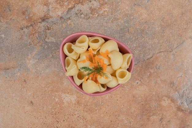 Pâtes en forme de coquillage avec des tranches de carottes et de l'aneth dans un bol
