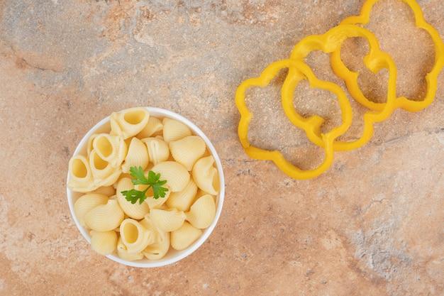 Pâtes en forme de coquillage et tranches de poivron sur fond orange