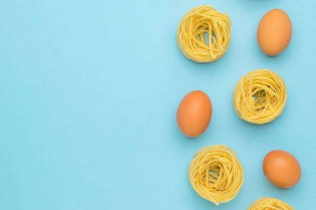 Pâtes en forme de nids et d'oeufs sur fond bleu. espace pour votre texte. ingrédients pour faire des pâtes.