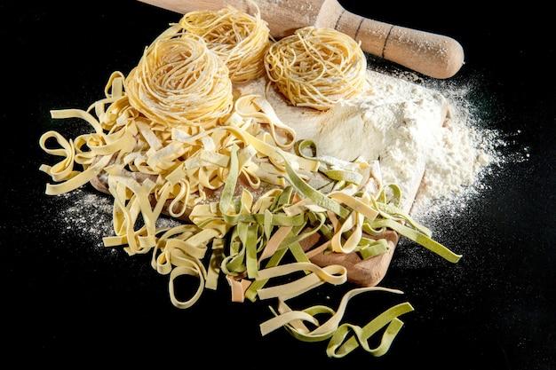 Les pâtes fraîchement cuites reposent sur une surface sombre saupoudrée de farine. pâtes italiennes. tagliatelles. pâtes crues. recette de pâtes italiennes. vue de dessus, copiez l'espace.