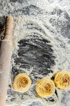 Les pâtes fraîchement cuites reposent sur une surface sombre saupoudrée de farine. pâtes italiennes.
