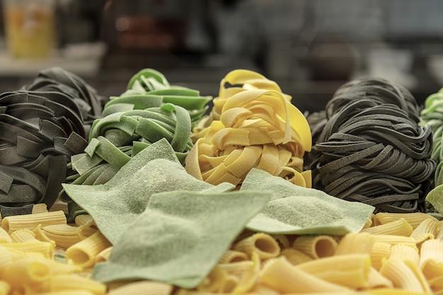 Des pâtes fraîches non cuites et des raviolis maison aux épinards et à l'encre de seiche sont enroulés sur la table.