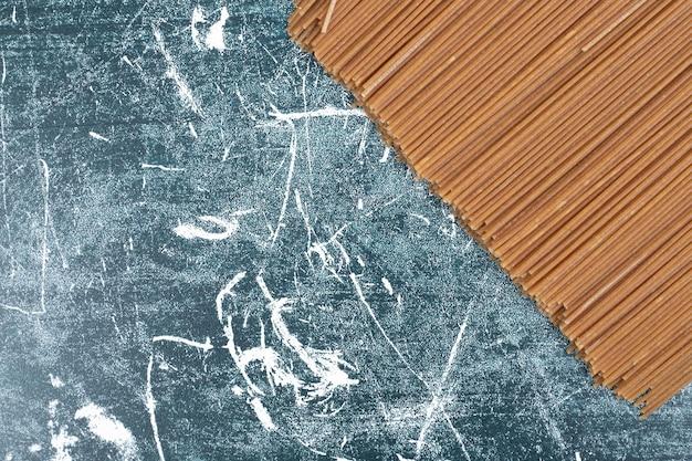 Pâtes fraîches non préparées sur l'espace de marbre.
