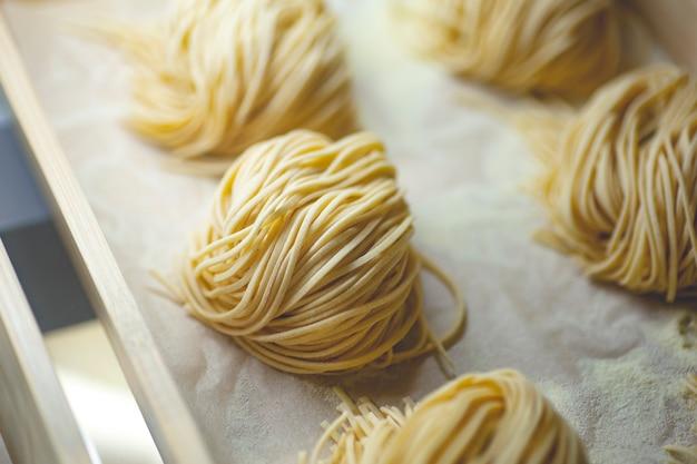 Pâtes fraîches. pâtes italiennes faites maison faites à la main avec des ingrédients frais, des œufs et de la farine de blé. photo de haute qualité
