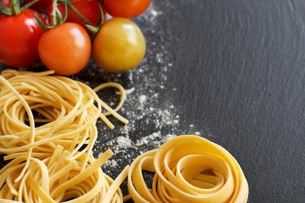 Pâtes fraîches et tomates sur un tableau noir