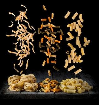 Pâtes fraîches tombant sous différentes formes et couleurs sur un bois