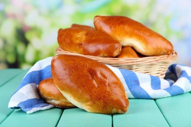 Pâtés frais cuits au four dans le panier en osier, sur lumineux