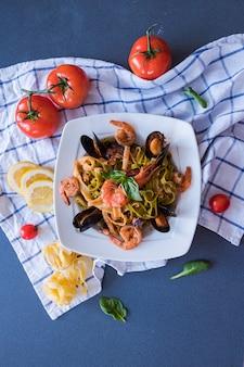 Pâtes de fruits de mer aux moules et aux crevettes sur une plaque blanche. spaghetti sur fond bleu