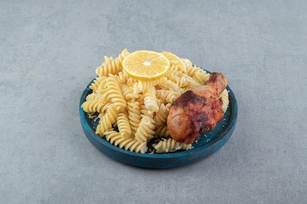 Pâtes fusilli au poulet frit sur plaque bleue.