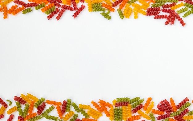 Pâtes fusilli multicolores sur fond blanc, orientation horizontale, espace copie, vue de dessus