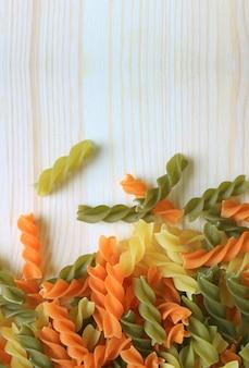 Pâtes fusilli tricolores sur table en bois