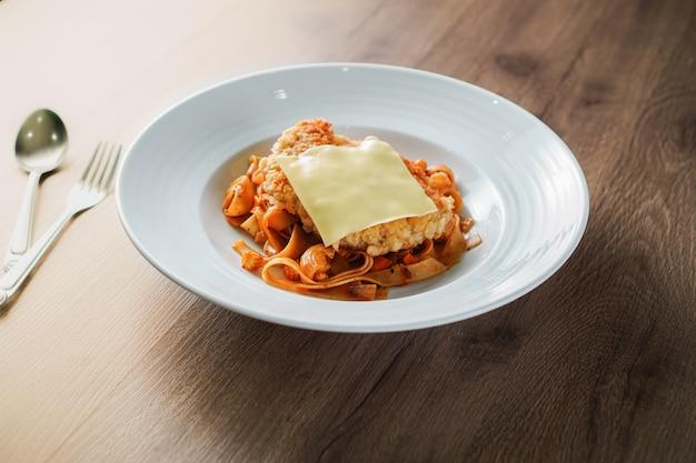 Pâtes avec garniture à la sauce tomate, escalope de porc croustillante frite et une feuille de fromage