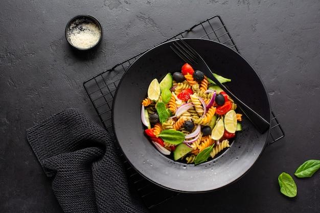 Pâtes de grains entiers avec des légumes sur une plaque blanche sur fond d'ardoise noire, de pierre ou de béton. vue de dessus avec espace de copie.